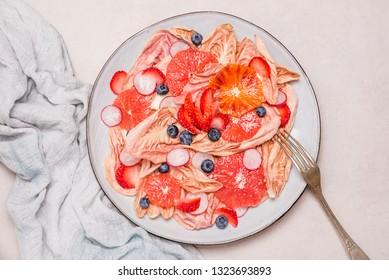 Healthy detox vegan salad.Pink radicchio with oranges, radish, strawberry and blueberry.