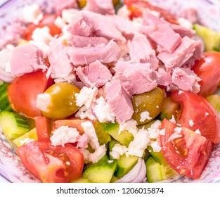 Healthy diabetic eating: Simple salad made with cucumber, ham, tomatoes, garlic stuffed olives and onions.