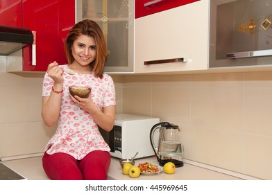 Healthy diet. Beautiful smiling woman eating porridge in modern kitchen. Healthy eating, food and lifestyle concept. Health, beauty, dieting concept.