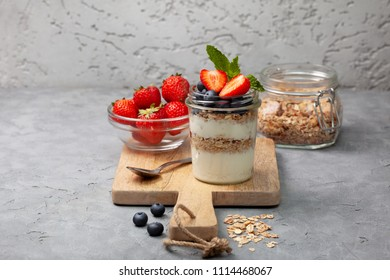 healthy diet breakfast. granola, yoghurt, blueberries , strawberries in a jar on a gray concrete background. copy space