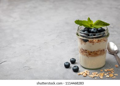 healthy diet breakfast. granola, yoghurt, blueberries in a jar on a gray concrete background. copy space