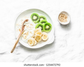 Healthy diet breakfast - greek yogurt with honey and fruit on a light background, top view. Copy space