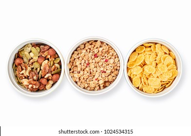 Healthy diet breakfast ingredients: corn flakes, mixed seeds and nuts, muesli isolated on white background. Modern minimalism style, top view