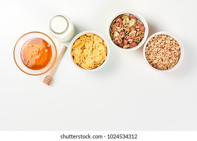 Healthy diet breakfast ingredients: honey, corn flakes, mixed seeds and nuts, muesli and bottle of milk with empty glass on white background. Modern minimalism style, top view