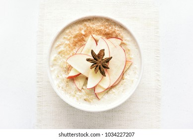 Healthy diet breakfast. Oats porridge with red apple slices and cinnamon. Top view, flat lay