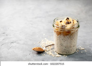 healthy diet breakfast. overnight oatmeal with chia seeds, bananas, peanut butter, honey, chocolate sprinkling in a glass jar on a gray concrete background