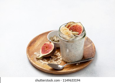 healthy diet breakfast. overnight oatmeal with chia seeds and fruits: banana, figs, pumpkin seeds on a light background