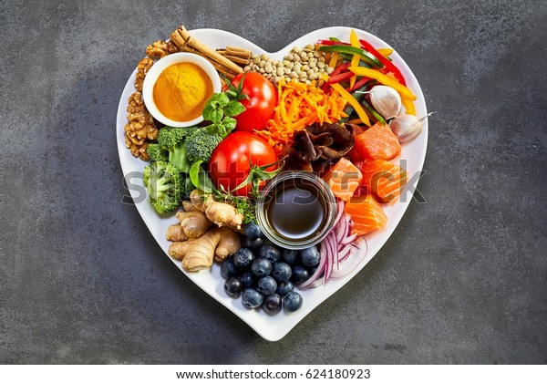 Healthy diet for the cardiovascular system with a heart-shaped plate of acai, lentils, soy sauce, ginger, salmon, carrot, tomato, turmeric, cinnamon, walnuts, garlic, peppers, broccoli, basil, onion
