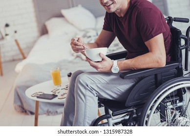 Healthy diet. Close up of a bowl with cereal being in hands of nice paralyzed man while keeping a special diet