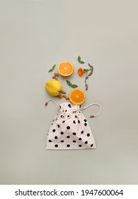Healthy diet concept, fruits, chia, almond, orange, quince and fresh leaves coming out of a cotton food bag, top view spring and freshness concept on green background