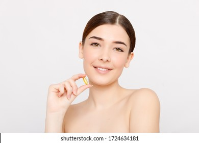 Healthy diet food. Beautiful smiling young woman holding a fish oil pill in her hand. Closeup. taking capsule. Vitamin and dietary supplements