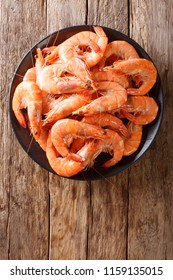 Healthy diet food: boiled wild tiger shrimps close-up on a plate on a table. vertical top view from above, rustic