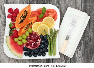 Healthy diet food with fresh fruit and vegetable on a plate with fork and napkin on rustic wood table background. Super foods high in antioxidants, anthocyanins, dietary fibre and vitamins.
