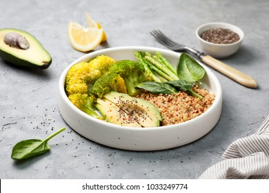 healthy diet food. kinoa with vegetables: broccoli, asparagus, avocado, spinach in a white bowl on a gray concrete background