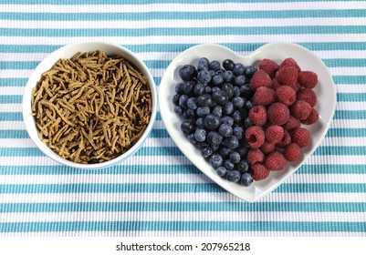 Healthy diet high dietary fiber breakfast with bowl of bran cereal and berries on white heart plate on aqua blue and white place mat.