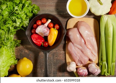 Healthy diet Italian lifestyle: Mediterranean fruits vegetables herbs spices and chicken meat. Top view. Wooden rustic background. Free space text layout.