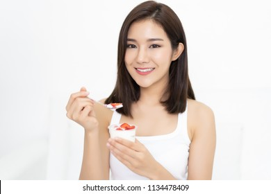 Healthy Diet And Nutrition. Portrait of beautiful young Asian woman eating natural yogurt at home and looking at camera.Weight Loss Food Concept. High Resolution