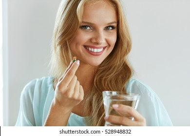 Healthy Diet Nutrition. Portrait Of Beautiful Smiling Young Woman Taking Vitamin Pill. Closeup Of Happy Girl Holding Colorful Capsule Pill And Glass Of Fresh Water. Dietary Supplement. High Resolution
