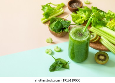 Healthy diet and nutrition, vegan, alkaline, vegetarian concepts. Green smoothie with celery, kiwi and spinach on a green pink background. Copy space.