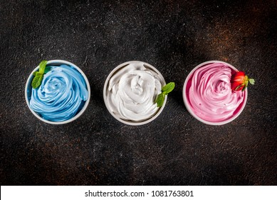 Healthy diet summer dessert, vanilla and berry frozen yogurt or  soft ice cream in white bowls, white marble background copy space above
