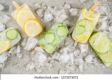 Healthy diet summer dessert, Vegan trendy ice cream. Sweet and sour infused water popsicles with cucumber, lime and lemon slices, Grey stone background copy space
