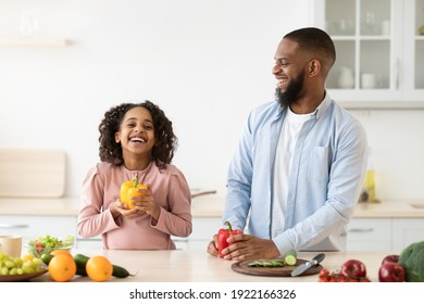 Healthy Diet And Vitamins. Portrait of happy african american girl helping dad to prepare vegetarian salad, holding fresh pepper. Smiling man and heerful daughter cooking together at home