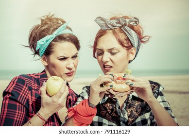 healthy diet vs junk food concept. two girls  eating foods looking disgusted and sarcastic at girlfriends junk food. retro style color filters.