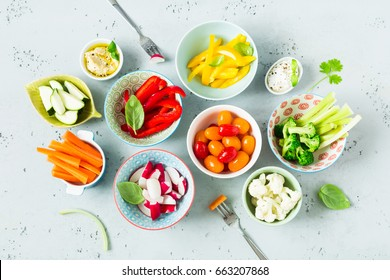 Healthy dietetic vegetarian starter (appetizer), snack or party food - fresh colorful organic sliced vegetables and dips. Bowls captured from above (top view, flat lay). Grey stone background.