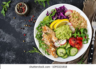 Healthy dinner. Buddha bowl lunch with grilled chicken and quinoa, tomato, guacamole, red cabbage, cucumber and arugula on gray background. Flat lay. Top view