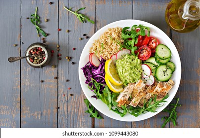 Healthy dinner. Buddha bowl lunch with grilled chicken and quinoa, tomato, guacamole, carrot, red cabbage, cucumber and arugula on wooden background. Flat lay. Top view