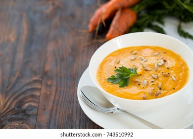 Healthy dinner with carrot soup-puree served in white bowl