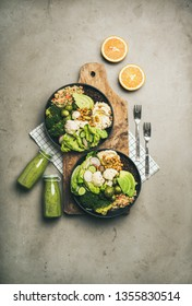 Healthy dinner, lunch setting. Flat-lay of vegan superbowls or Buddha bowls with hummus, vegetables, fresh salad, beans, couscous and avocado on board and green smoothies in bootles, top view