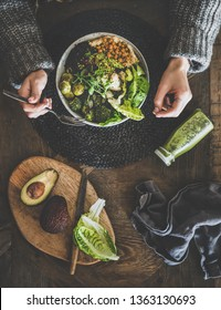 Healthy dinner or lunch setting. Flat-lay of vegan superbowl or Buddha bowl with hummus, vegetables, fresh salad, beans, couscous and avocado, green smoothie and woman's hands over table, top view