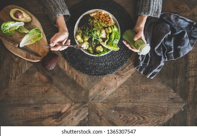 Healthy dinner, lunch setting. Flat-lay of vegan superbowl or Buddha bowl with hummus, vegetable, salad, beans, couscous and avocado, smoothie and woman's hands over wooden table, top view, copy space