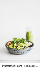 Healthy dinner or lunch. Vegan superbowl or Buddha bowl with hummus, vegetable, fresh salad, beans, couscous and avocado and green smoothie in bottle over white background, copy space