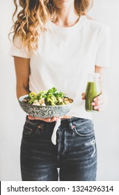 Healthy dinner, lunch. Woman in jeans standing and holding vegan superbowl or Buddha bowl with hummus, vegetable, fresh salad, beans, couscous and avocado and green smoothie in bottle