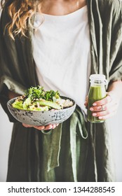 Healthy dinner or lunch. Woman in linen shirt standing and holding vegan superbowl or Buddha bowl with hummus, vegetable, fresh salad, beans, couscous and avocado and smoothie in hands
