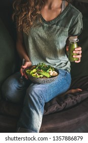Healthy dinner or lunch. Woman in t-shirt and jeans sitting and holding vegan superbowl or Buddha bowl with hummus, vegetable, salad, beans, couscous and avocado and smoothie in hands