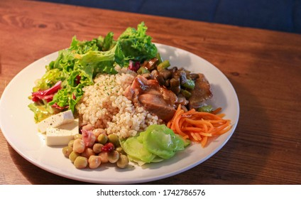Healthy dish on a white plate consisting of rice, beans, salad, cheese and sauteed chicken