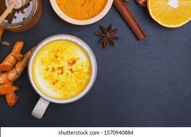 Healthy drink golden turmeric latte in a mug. Cinnamon sticks, turmeric powder and honey on black cement background. Detox turmeric tea and ingredients.