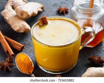 Healthy drink golden turmeric latte in glass cup.Gold milk with turmeric,ginger root,cinnamon sticks,dried turmeric powder and honey over black cement background.Detox turmeric tea and ingredients.