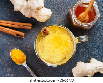 Healthy drink golden turmeric latte in glass cup.Gold milk with turmeric,ginger root,cinnamon sticks,turmeric powder and honey on black background.Detox turmeric tea and ingredients.Top view flat-lay.
