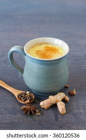 Healthy drink made from turmeric roots, exotic spices  with milk and honey