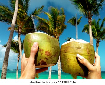 Healthy drink on a Caribbean beach. Pineapple and coconut handheld on the beach among palm trees.
