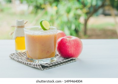 Healthy drink, Reduce cholesterol in the blood vessels of smoothies with red apple and lemon, Honey bottle in a glass on white wooden background