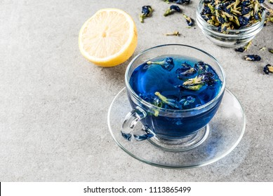 Healthy drinks, organic blue butterfly pea flower tea with limes and lemons, grey concrete background copy space