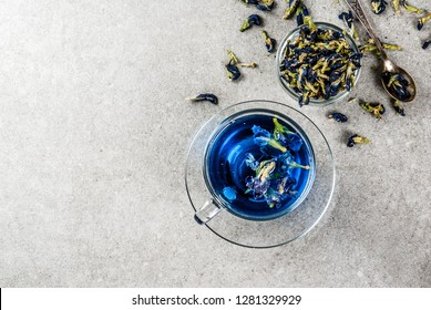 Healthy drinks, organic blue butterfly pea flower tea with limes and lemons, grey concrete background copy space top view