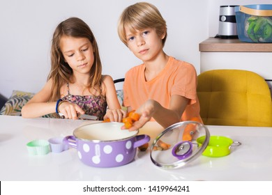 Healthy eating. Adorable siblings,brother and sister prepares vegetable for lunch