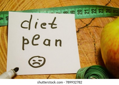 """Healthy eating. Apple, centimeter, a sticker with the inscription """"diet plan"""" and a sad smiley"""