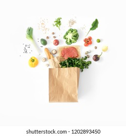 Healthy eating background, top view. Full paper bag of different health food on white background. Top view. Flat lay